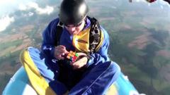 Парашутист решава кубчето на рубик докато лети в гумена лодка