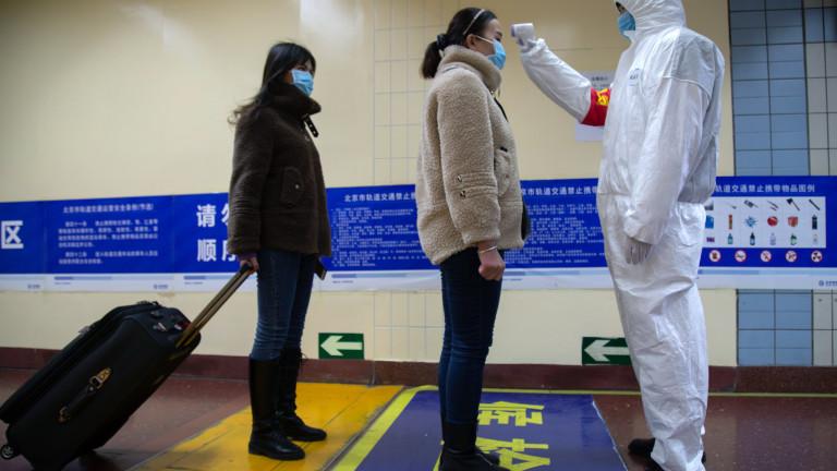 Медицински работник проверява температурата на хора в пекинското метро