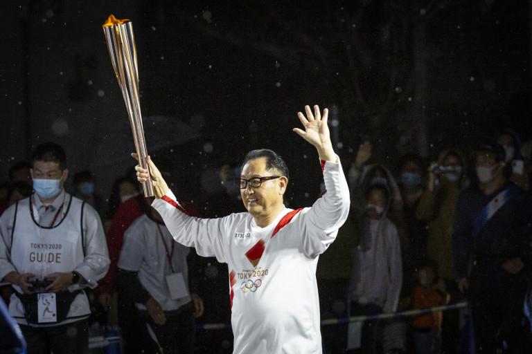 Акио Тойода с олимпийския огън през април